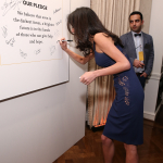Amal Clooney signs pledge wall at 100 LIVES launch in March 2015