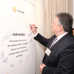 Noubar Afeyan signing pledge wall